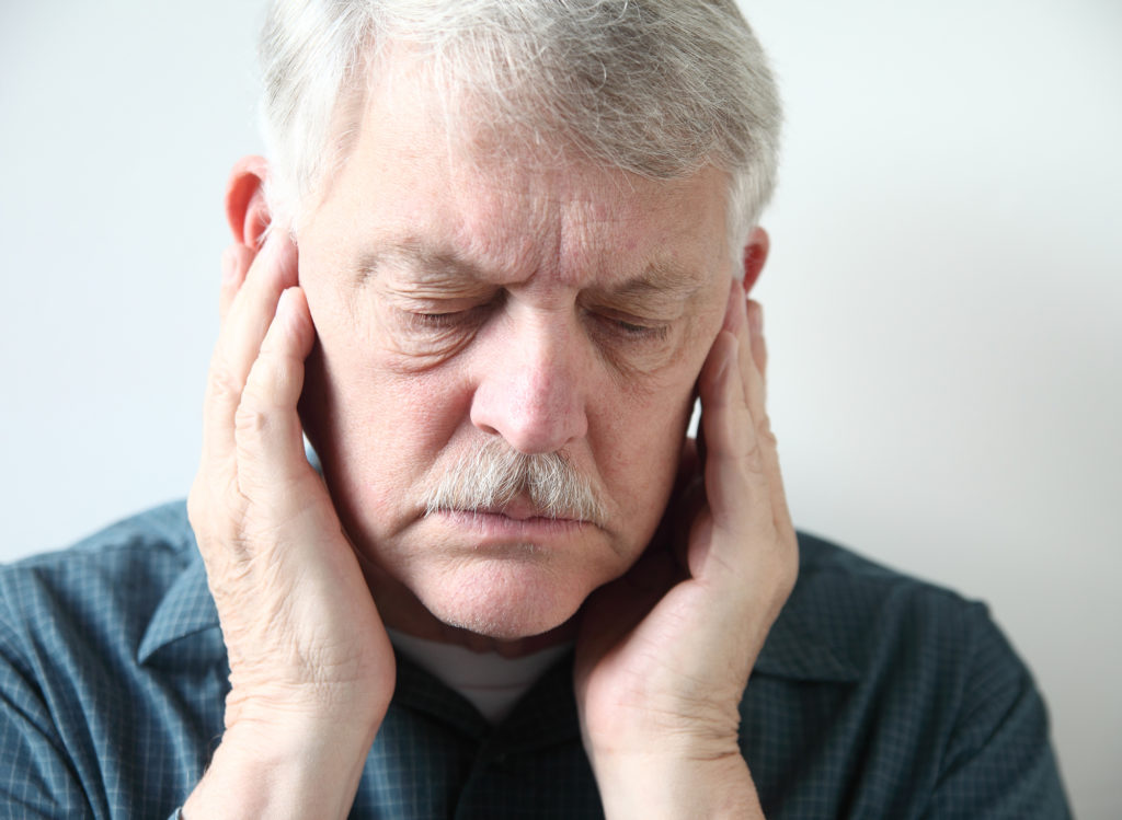 Older man hold the side of his face suffering from headaches due to TMJ.